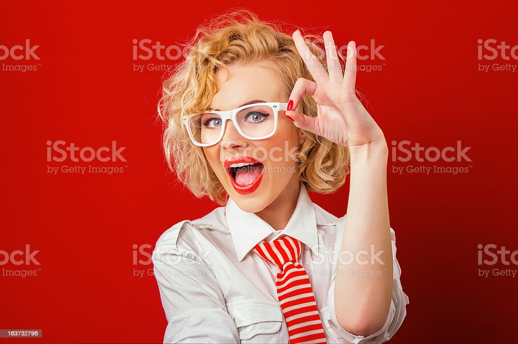 Smiling stylish woman showing sign excellently, isolated on red royalty-free stock photo