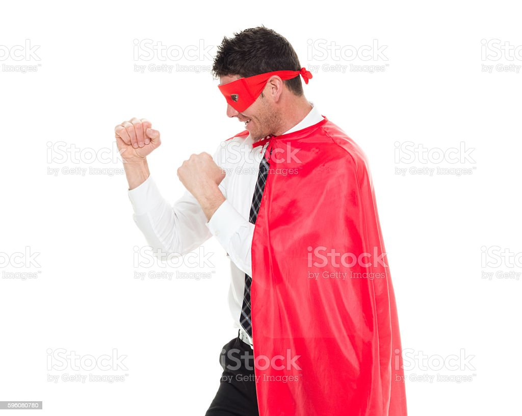 Smiling superhero in fighting stance stock photo