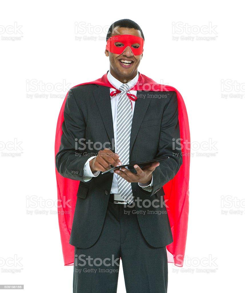 Smiling superhero using tablet stock photo