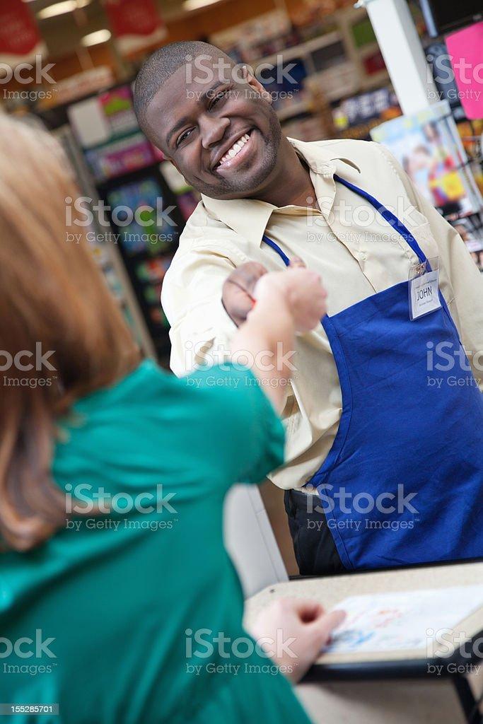 Smiling supermarket worker handing change to customer royalty-free stock photo
