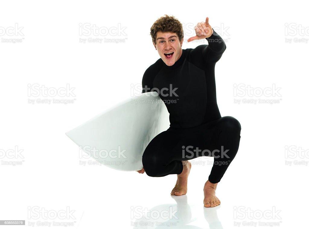 Smiling surfer giving shaka sign stock photo