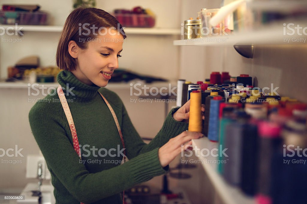 Smiling tailor looking at thread spools in clothing design studio. stock photo