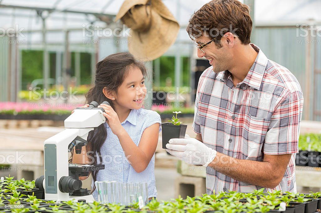Smiling teacher and student learning about plants stock photo