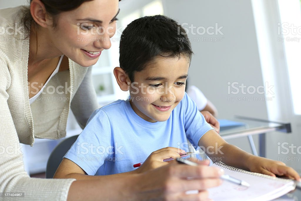 Smiling teacher helping kid stock photo