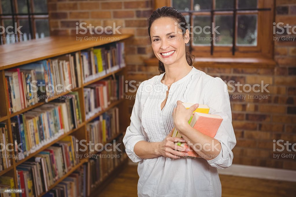 Smiling teacher holding books in her hands stock photo