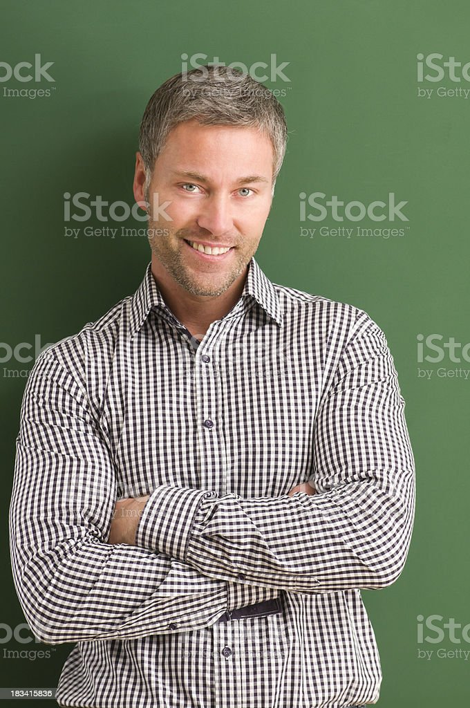 smiling teacher with arms crossed at blackboard royalty-free stock photo