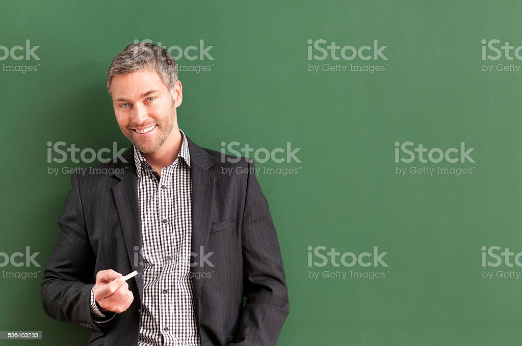 smiling teacher with grey hair at blackboard stock photo