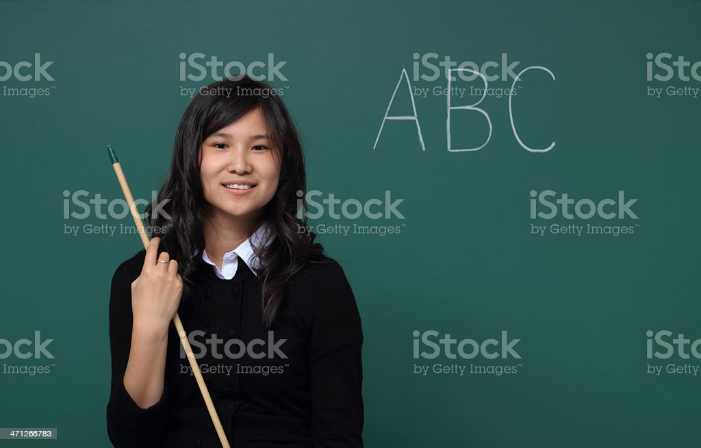 Smiling teacher with pointer and chalkboard royalty-free stock photo