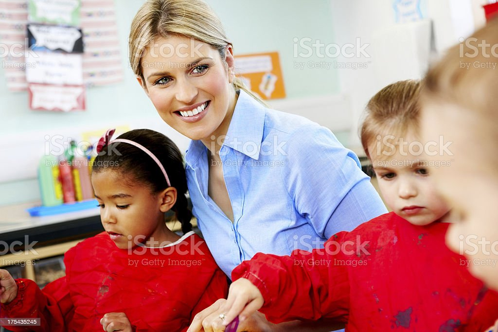 Smiling teacher with preschoolers in art class royalty-free stock photo