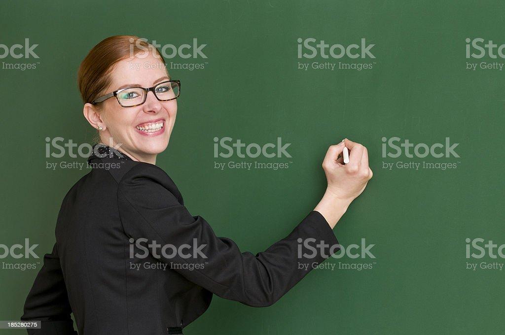 smiling teacher writing at blackboard royalty-free stock photo