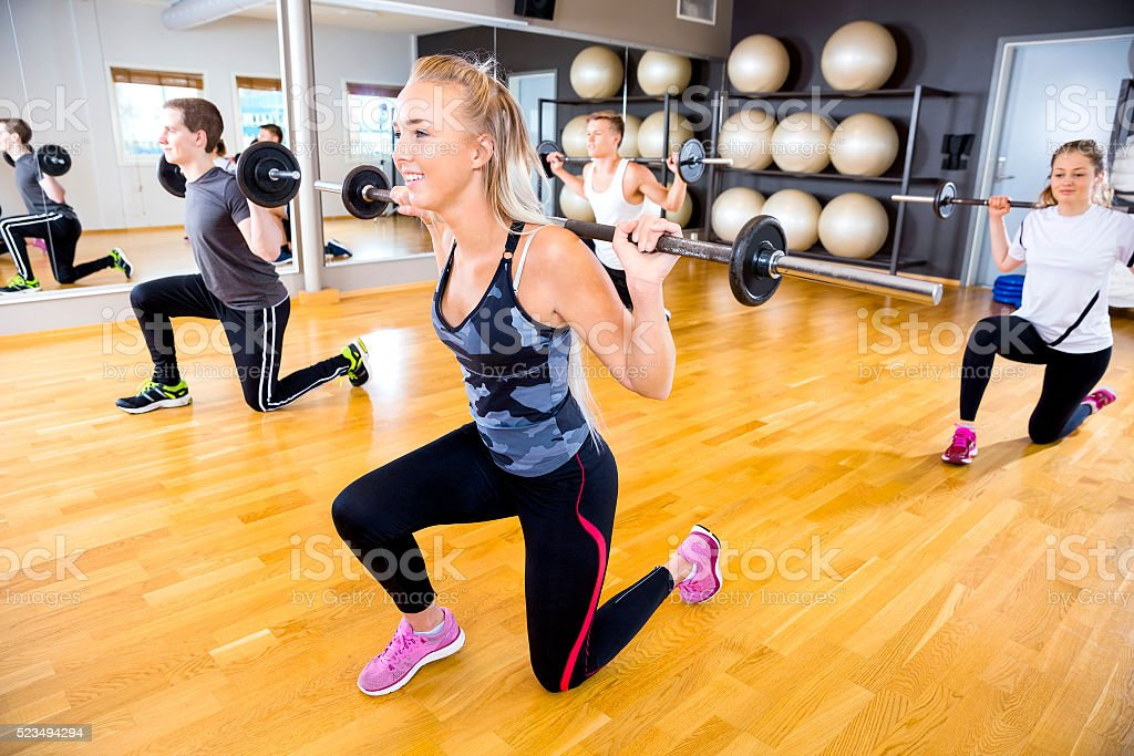 Smiling team doing split squats with weights at fitness gym stock photo