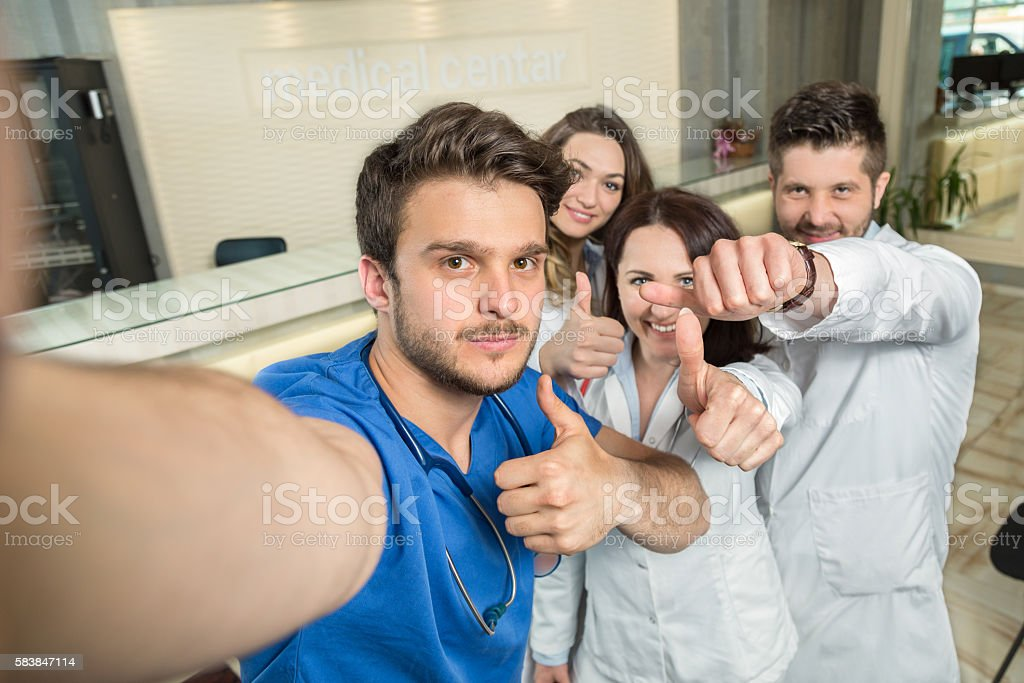 Smiling Team Of Doctors And Nurses At Hospital Taking Selfie stock photo