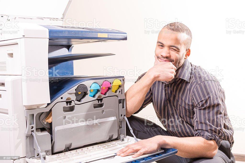smiling technician sitting near copier stock photo
