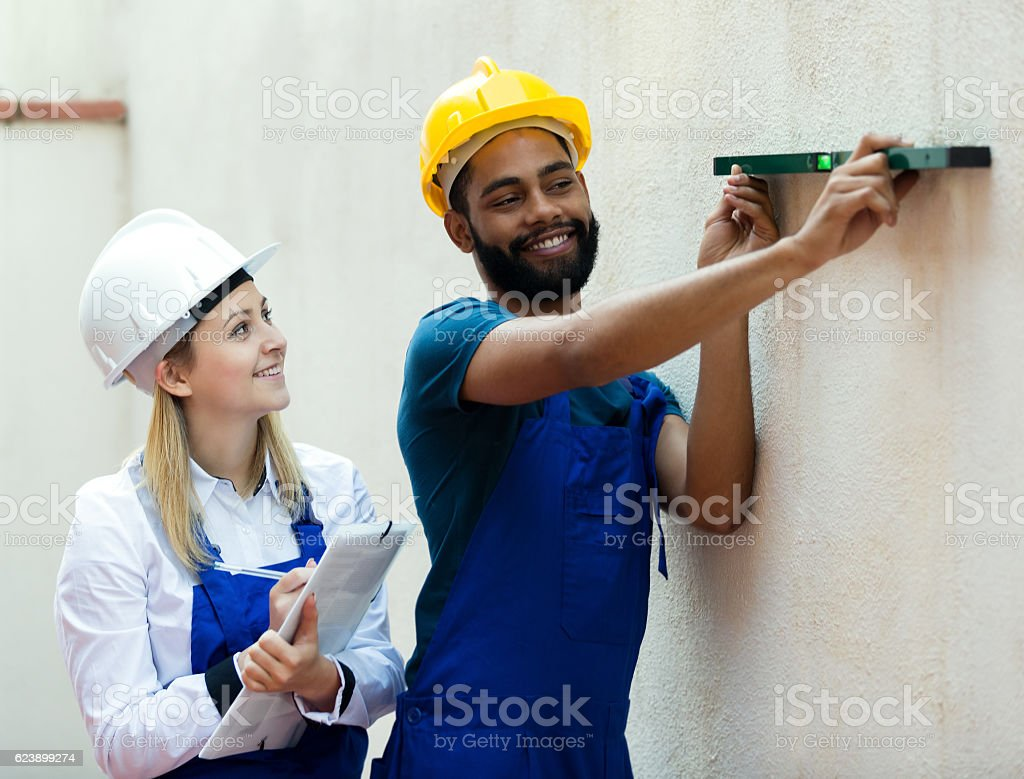Smiling technicians smoothing the wall stock photo