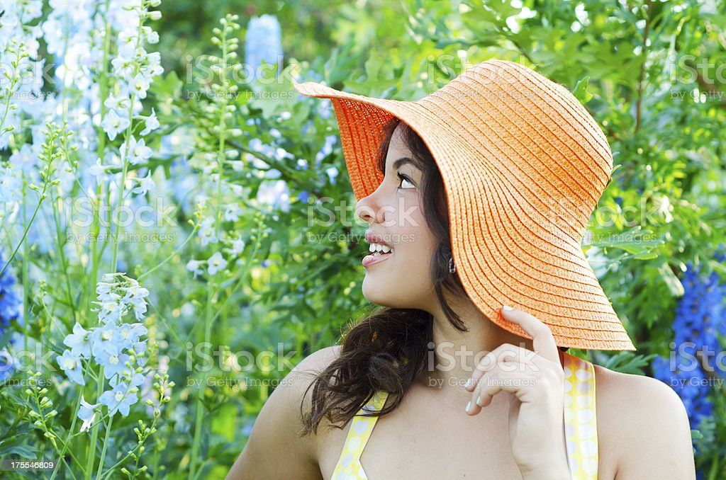 Smiling teen in orange hat looking at flowers. stock photo