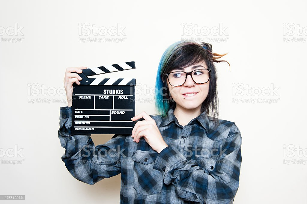 Smiling teen woman with clapper board stock photo