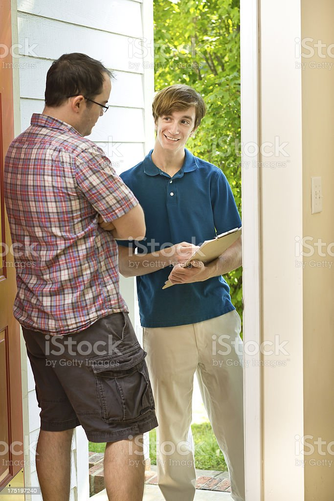 Smiling teenage boy canvassing and talking to a man at door royalty-free stock photo