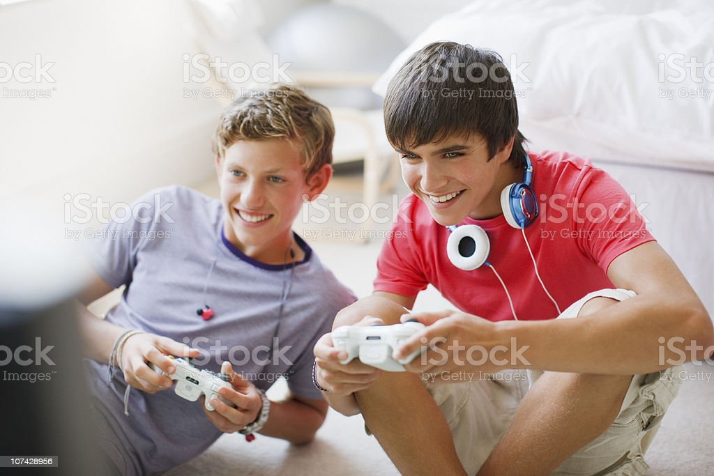 Smiling teenage boys playing video game stock photo