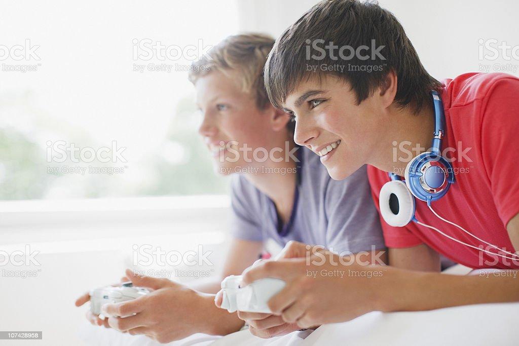 Smiling teenage boys playing video game royalty-free stock photo
