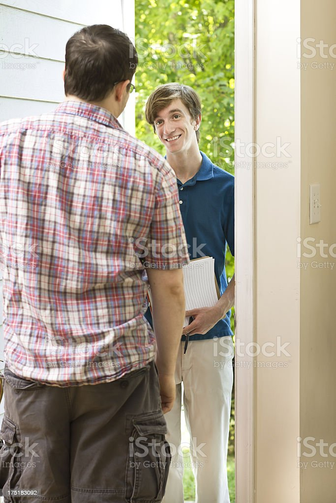 Smiling Teenage Canvasser Trying to Convince Man of His Agenda stock photo
