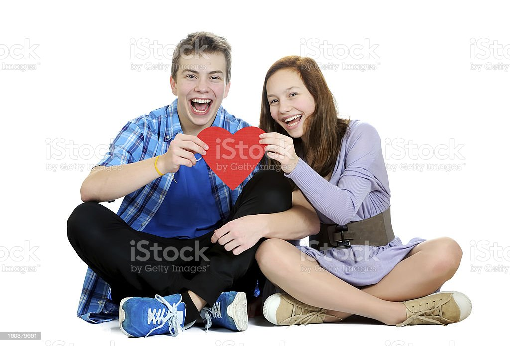 Smiling teenage girl and boy holding a valentine heart royalty-free stock photo