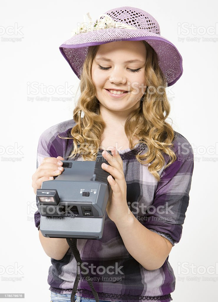 Smiling teenage girl holding a polaroid camera royalty-free stock photo