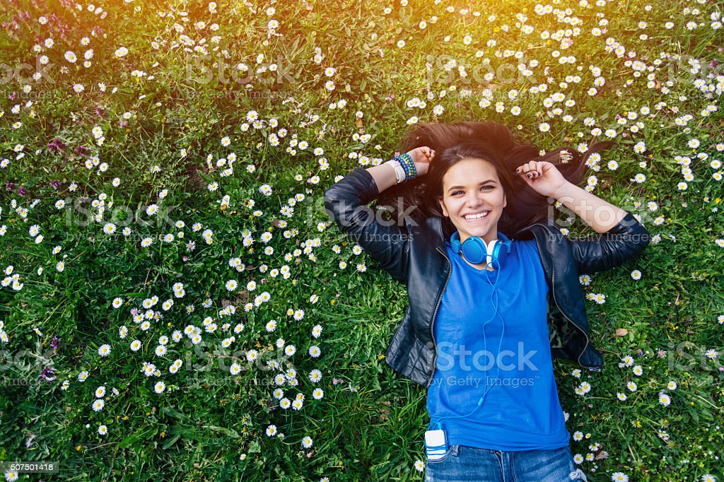 Smiling teenage girl lying down in the grass stock photo
