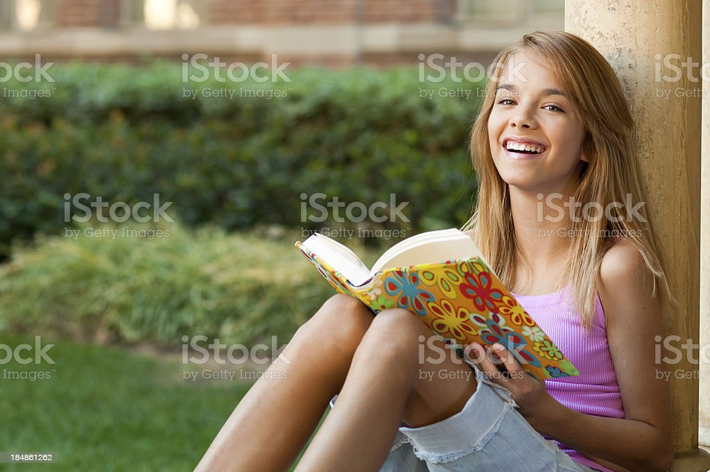 Smiling Teenage Schoolgirl With Book on School Campus royalty-free stock photo