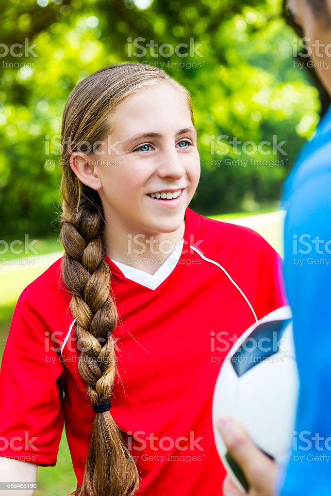 Smiling teenage soccer player talks with coach stock photo