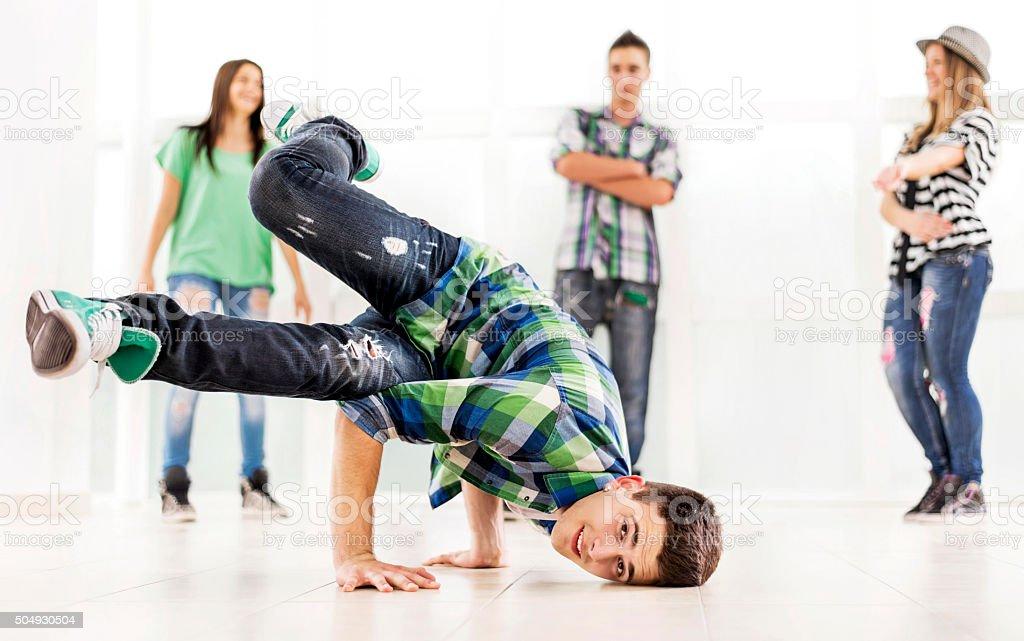 Smiling teenager break dancing and looking at camera. stock photo