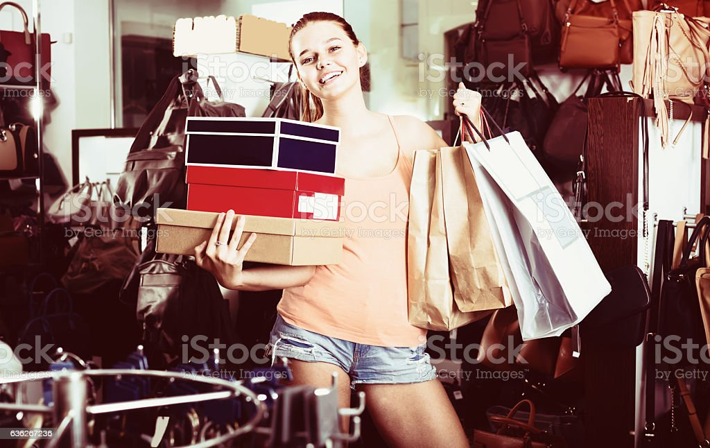 smiling teenager female holding boxes in shoes boutique stock photo