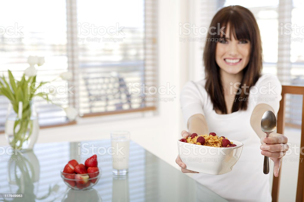 Smiling teenager holding a bowl of cereal royalty-free stock photo