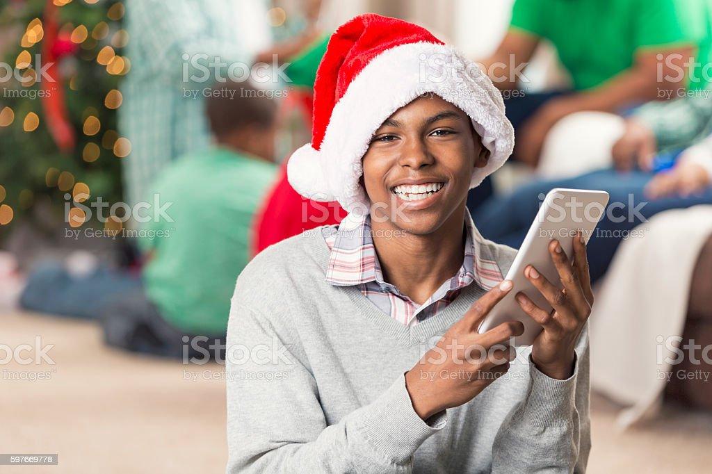 Smiling teenager holding digital tablet on Christmas morning stock photo