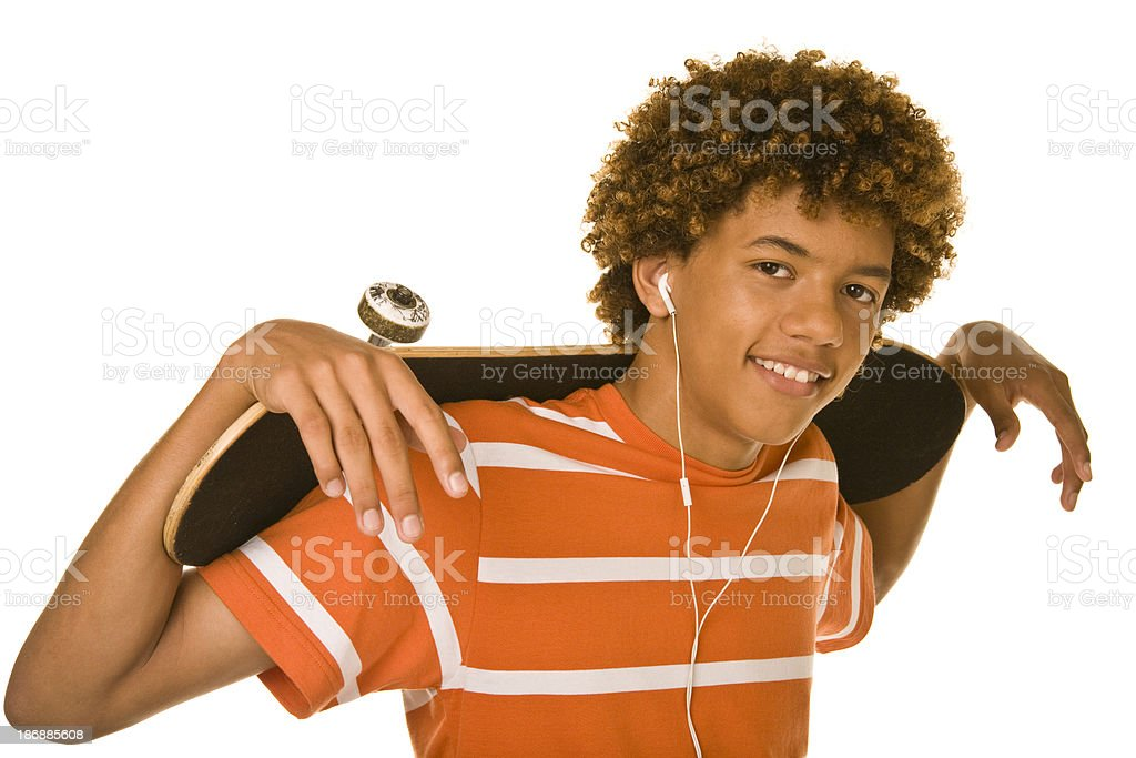 Smiling teenager with skateboard wearing earbuds royalty-free stock photo