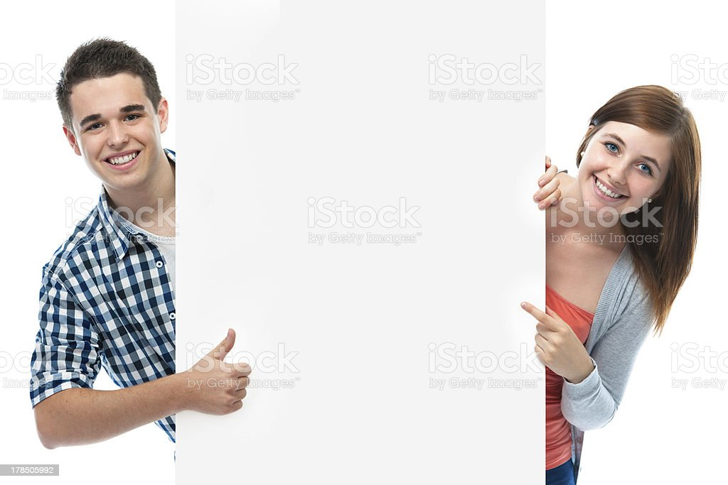 Smiling teenagers behind white wall stock photo