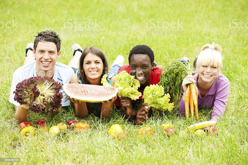 Smiling teenagers lying in grass, holding produce royalty-free stock photo
