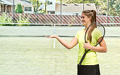 Smiling tennis player presenting in field