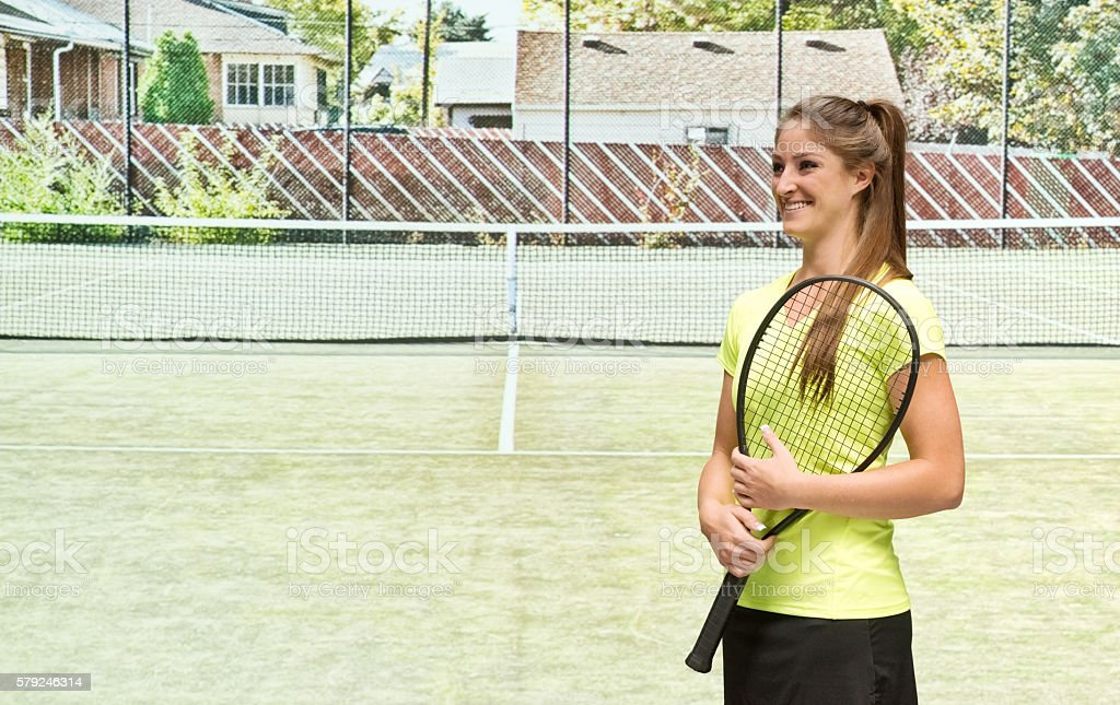 Smiling tennis player standing in field stock photo