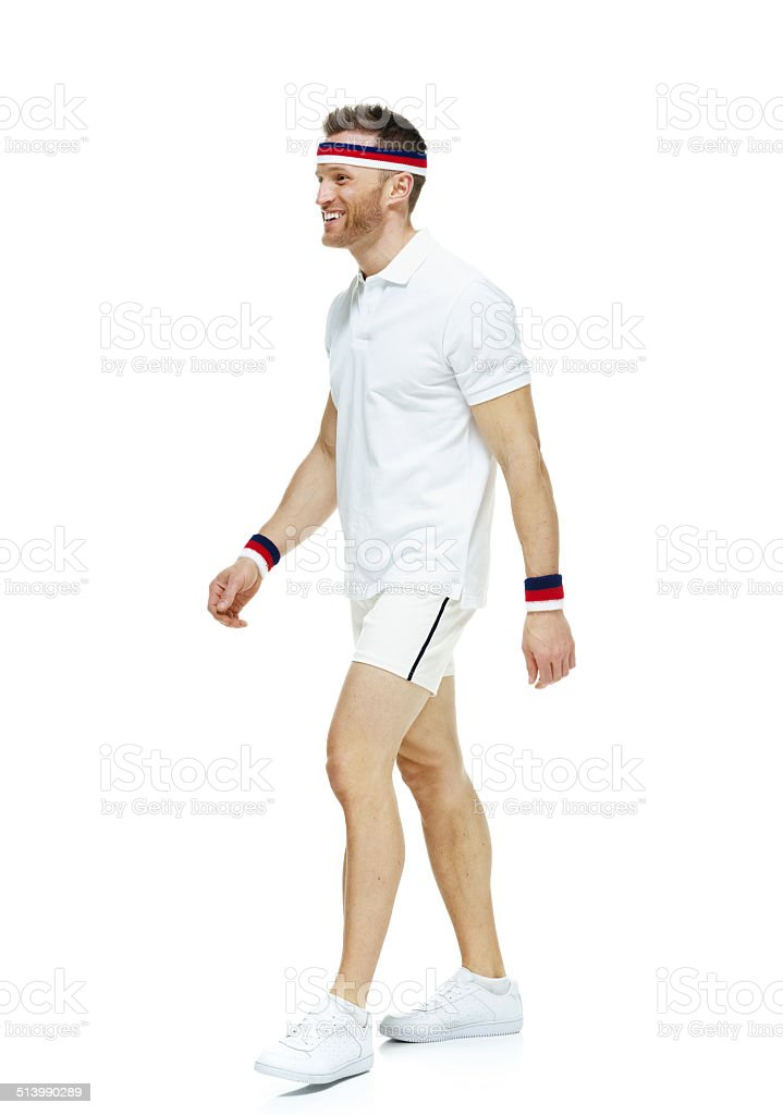 Smiling tennis player walking & looking away stock photo