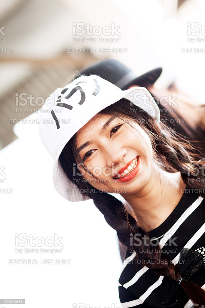 Smiling thai girl with cap and braids stock photo