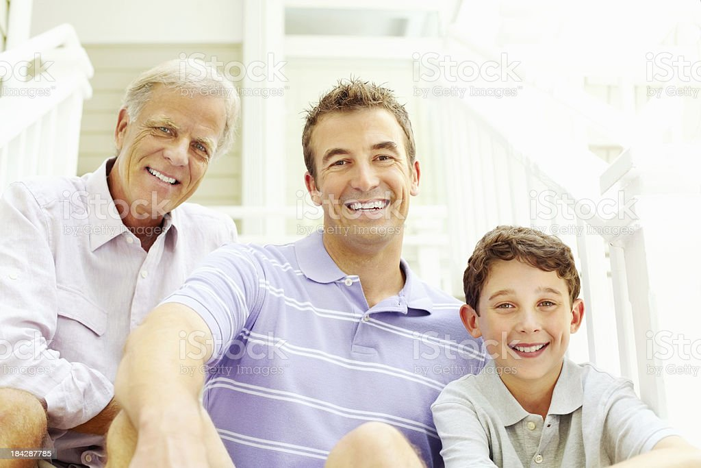 Smiling three generation family sitting on staircase royalty-free stock photo