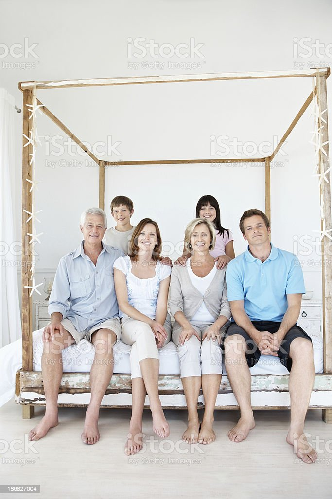 Smiling three generational family sitting together on a bed royalty-free stock photo