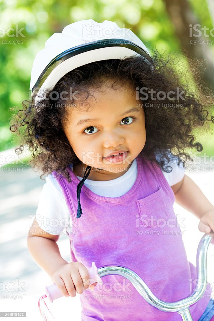 Smiling toddler girl on a tricycle in the park stock photo