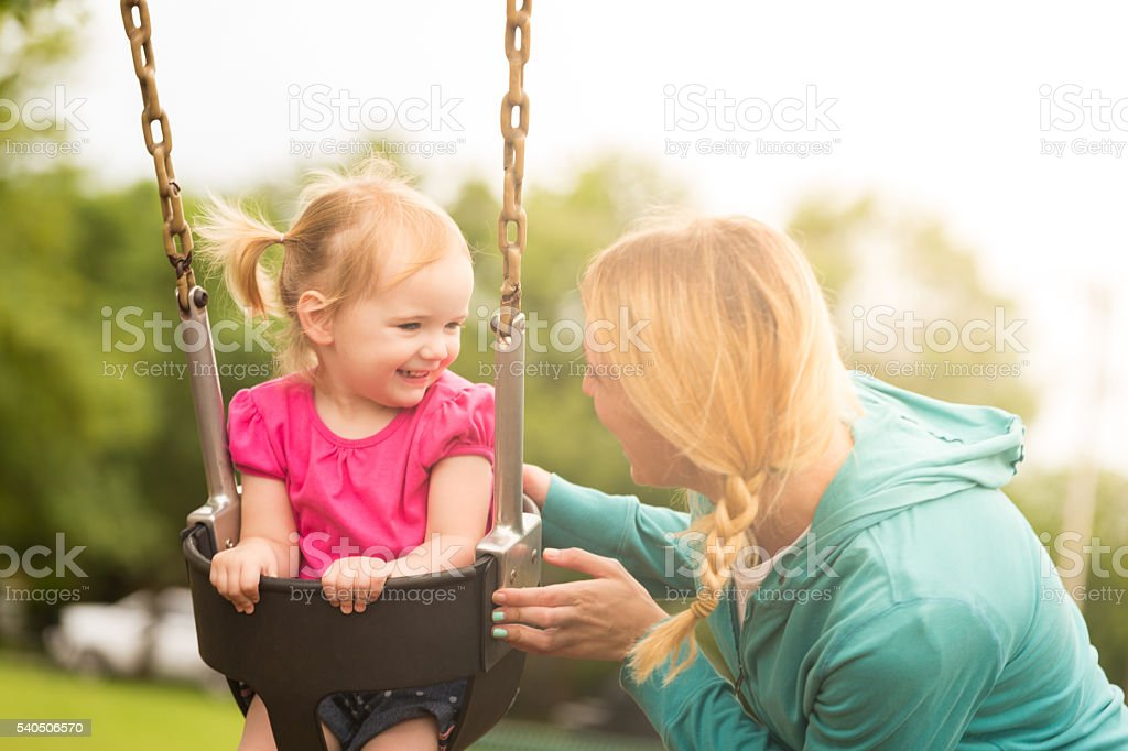 Smiling toddler girl on swing with mother stock photo