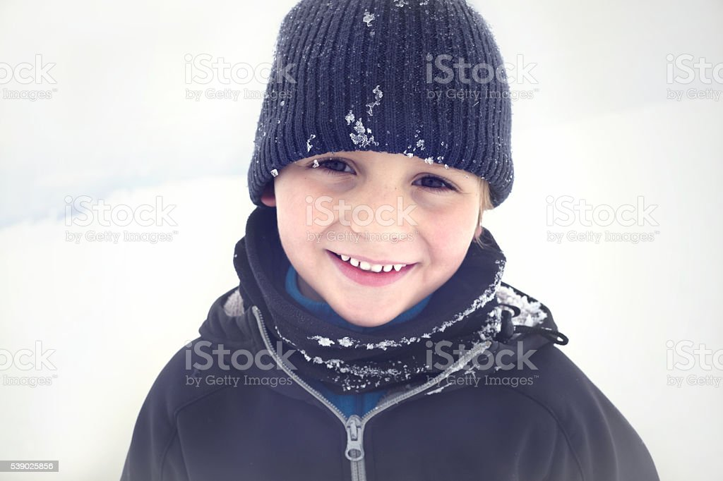 Smiling toddler posing for pictures in the snow stock photo