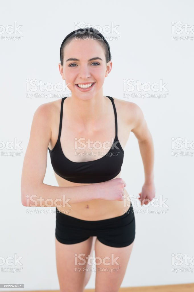 Smiling toned young woman hips in fitness studio stock photo
