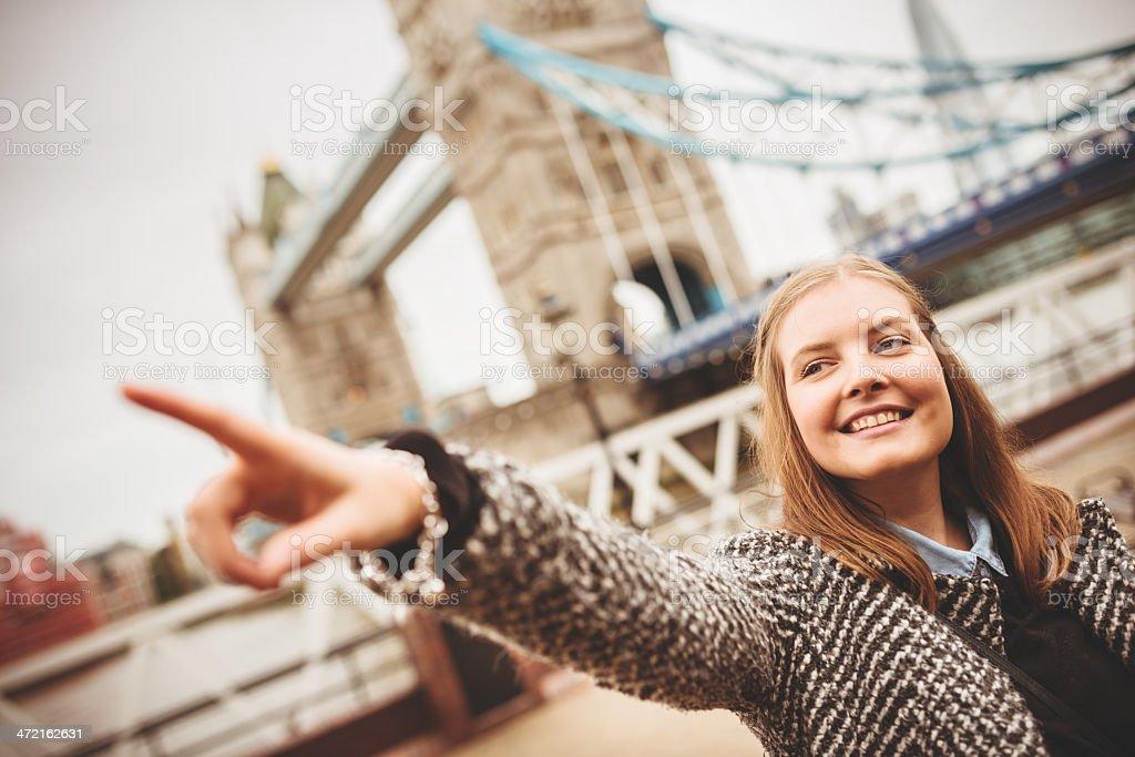 Smiling tourist in london under tower bridge royalty-free stock photo