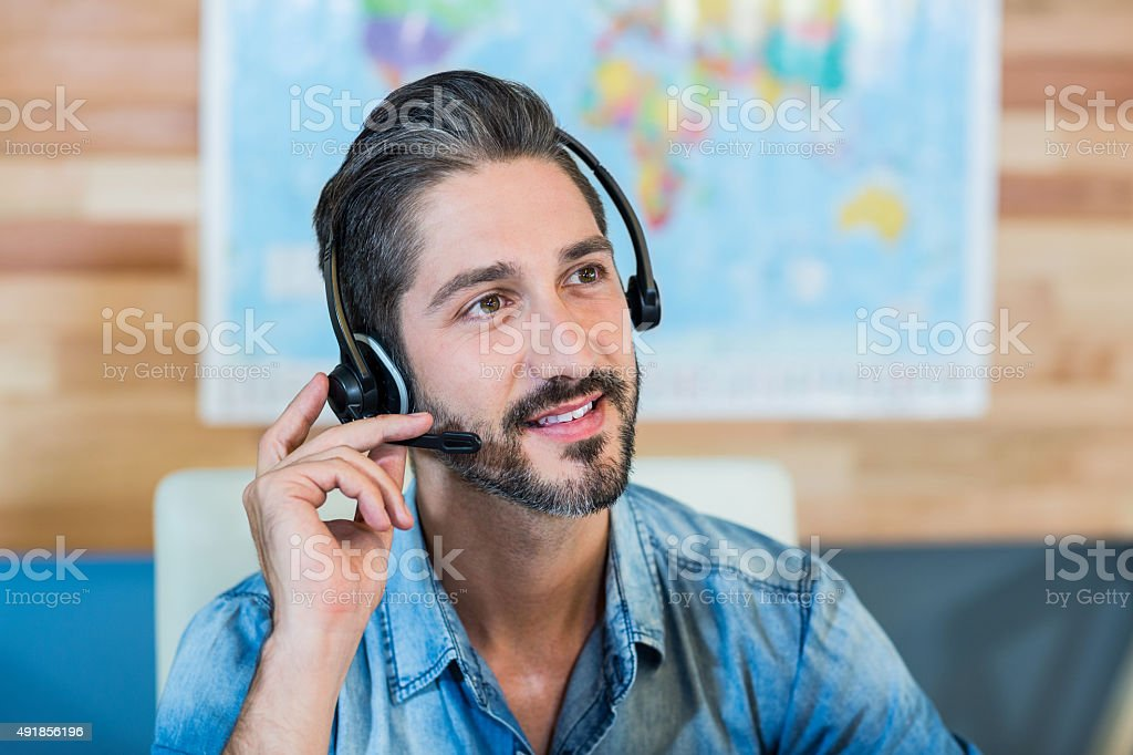 Smiling travel agent having phone call stock photo