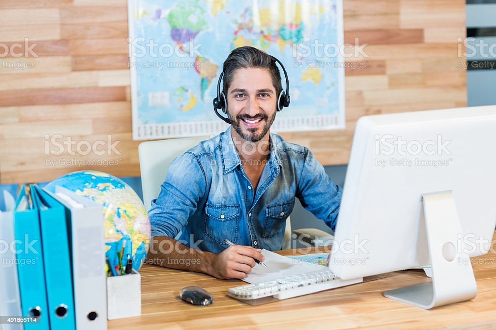 Smiling travel agent looking at camera stock photo