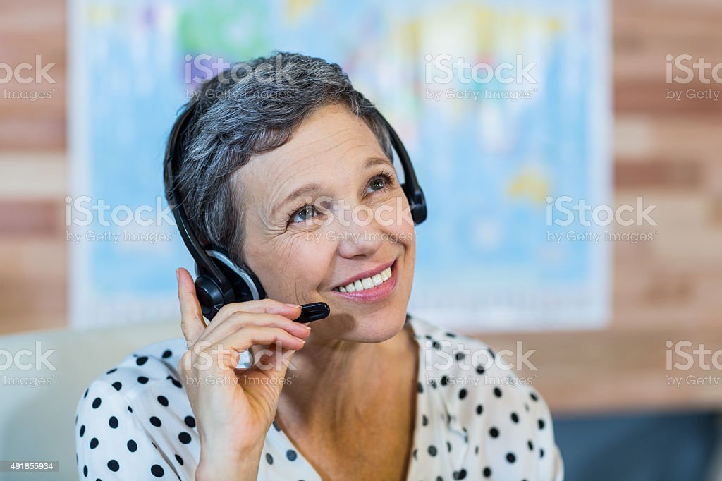 Smiling travel agent sitting at her desk stock photo
